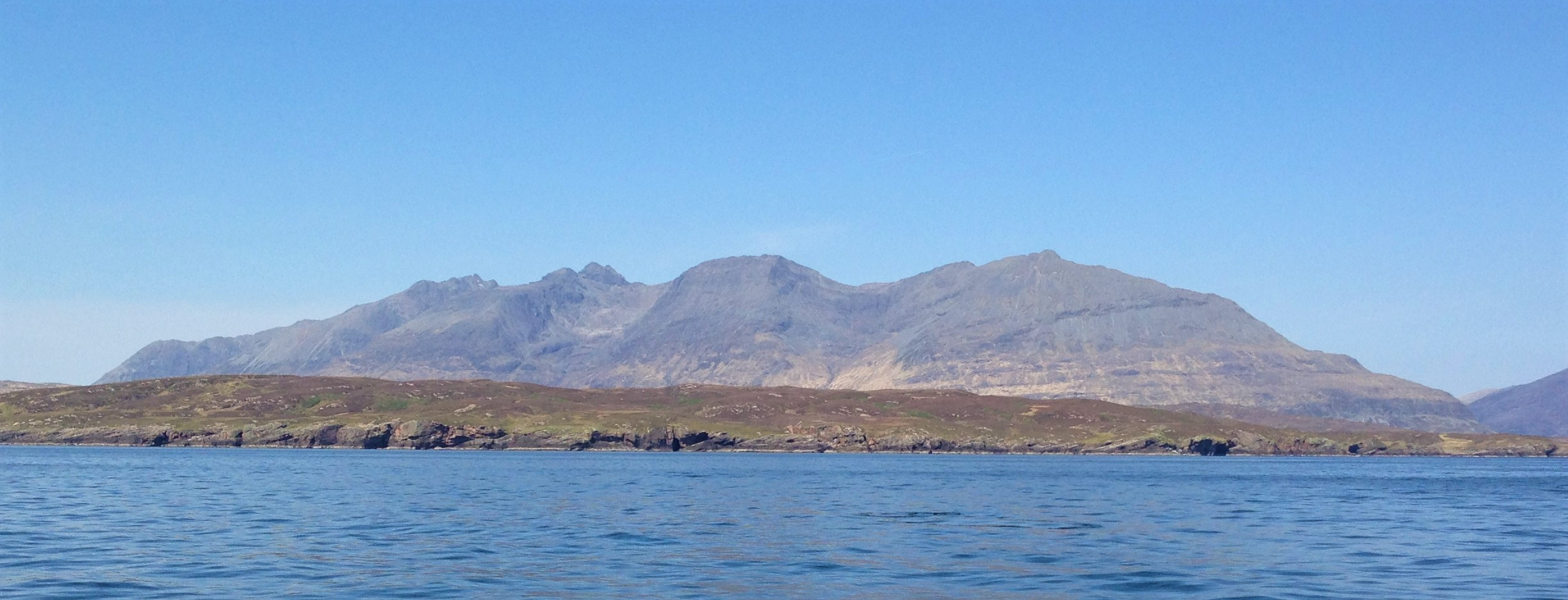 A photo from a boat showing the mountains of the isle of Rum just before a surprise sighting of whales