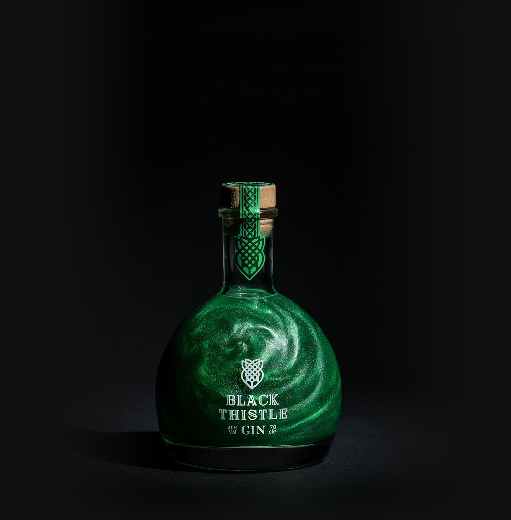 Green Shimmer Scottish Gin in its potion like bottle against a black background