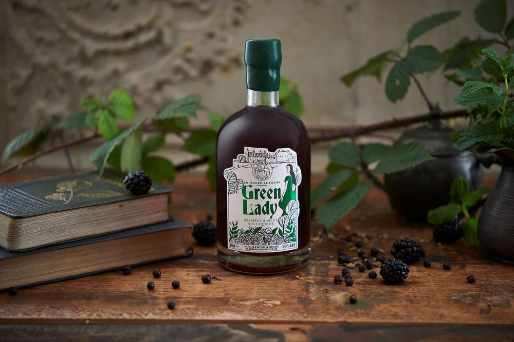 A bottle of Green LAdy Gin from the stirling distillery surrounded by brambles and mint leaves