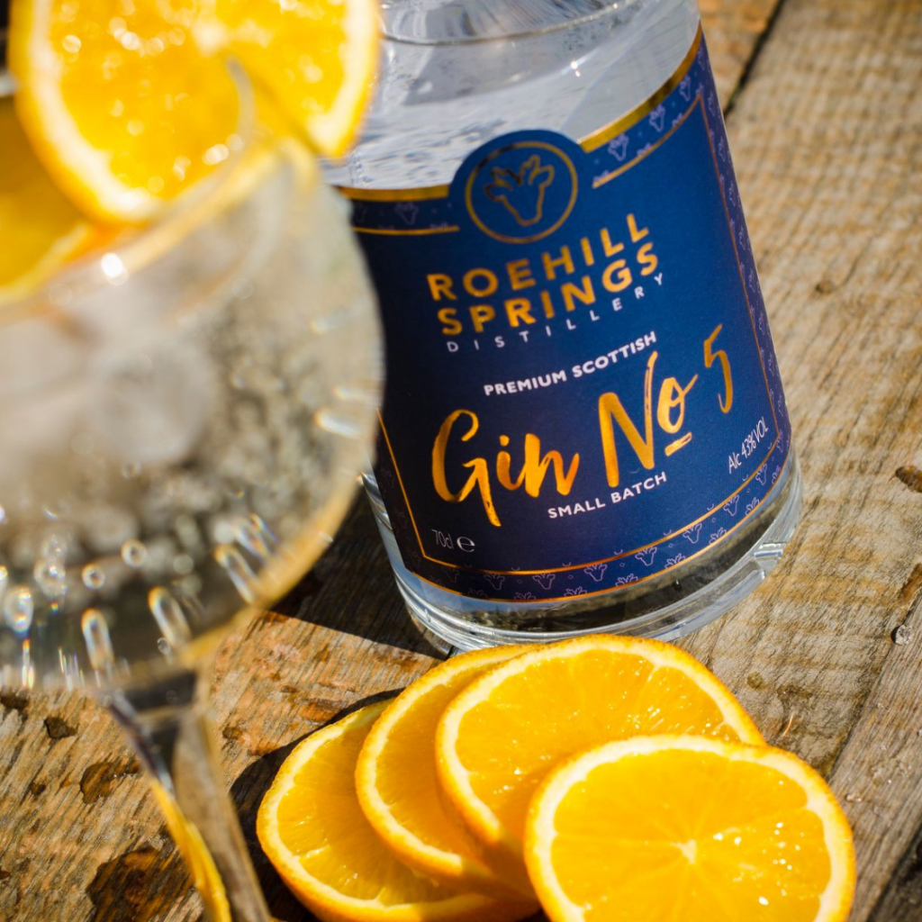Bottle of Roehill Springs Gin with a backgound of orange slices and a glass with a G&T