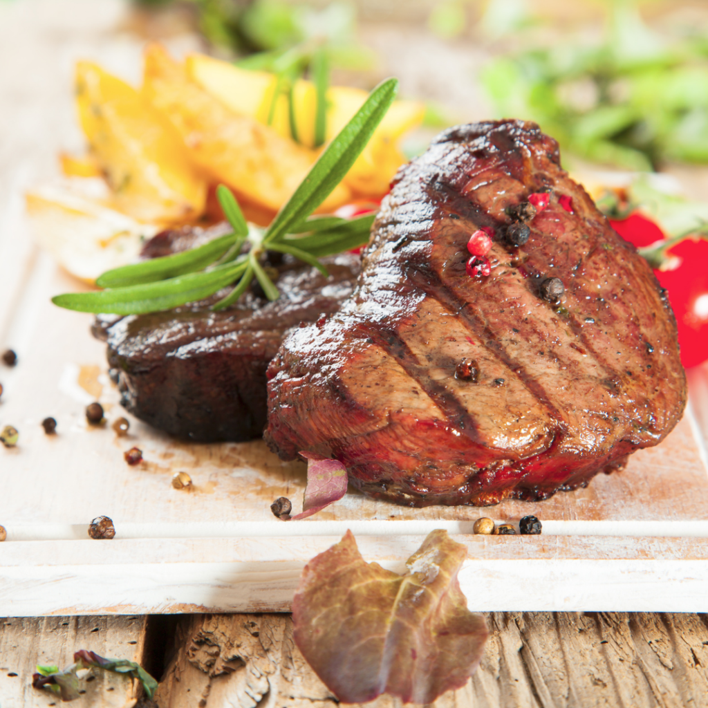 Plate of succulent steak with peppercorns and rosemary